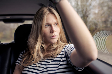 Young woman in car gazing through window