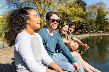 battersea: Four young adult friends sitting on lakeside in Battersea Park