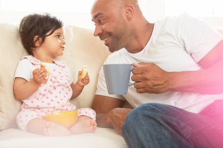 6 12 months: Baby girl and father sitting on sofa eating snack