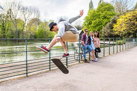 battersea: Young male skateboarder doing jump trick for friends in Battersea Park