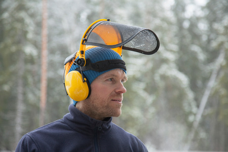Logger wearing safety visor in forest, Tammela, Forssa, Finland