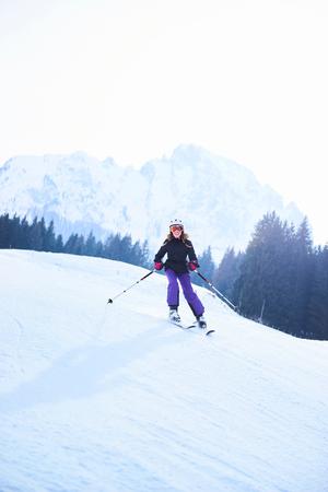 Teenage girl skiing down ski slope, Gstaad, Switzerland LANG_EVOIMAGES