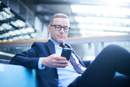 Businessman on sofa looking at smartphone in office atrium LANG_EVOIMAGES