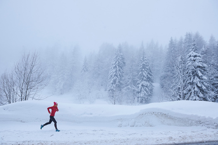 Distant view of female runner running in deep snow, Gstaad, Switzerland