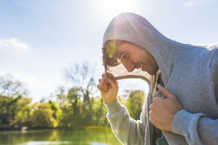 battersea: Young man holding hood on lakeside in Battersea Park LANG_EVOIMAGES