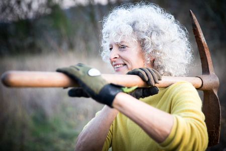 Mature woman with grey hair carrying pick axe over her shoulder in woodland