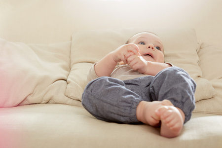 6 12 months: Baby boy lying on sofa