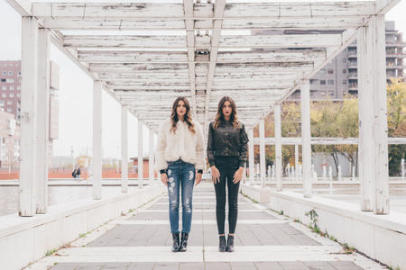 milánó: Portrait of twin sisters, in urban area, standing side by side LANG_EVOIMAGES