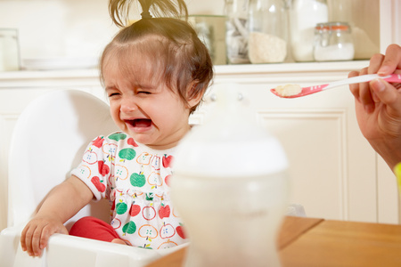 6 12 months: Baby girl crying while being fed breakfast by mother