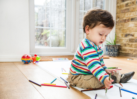 Male toddler sitting on floor drawing on long paper