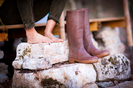 knee boots: Mature womans bare feet and knee high boots on stone porch steps
