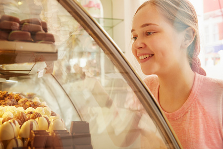 Girl in bakery looking at cakes in display cabinet smiling LANG_EVOIMAGES