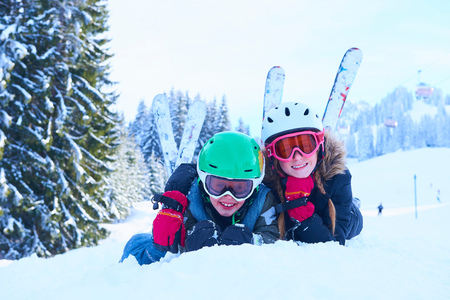 Portrait of skiing teenage girl and brother lying in snow, Gstaad, Switzerland
