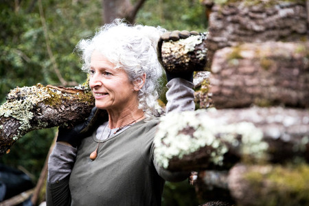 Mature woman carrying log on her shoulder in garden