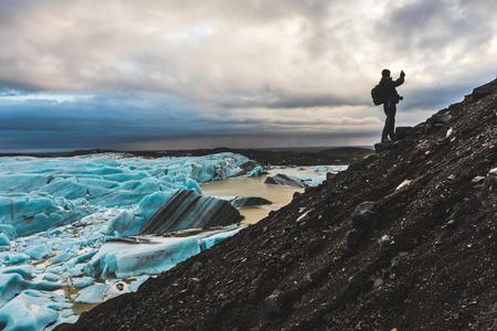 one mature man only: Man on hillside, photographing view, Svinafellsjokull glacier, Svinafellsjokull. Iceland
