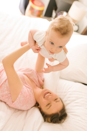 Mother and baby bonding on bed LANG_EVOIMAGES