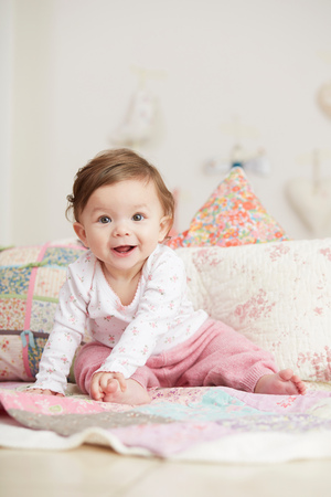 6 12 months: Portrait of baby girl, sitting on blanket, laughing