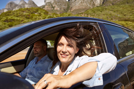 Couple in car, driving along rural road, woman leaning on open window