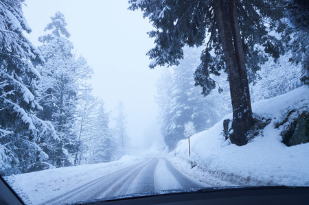 Windscreen view of snow covered rural forest road, Gstaad, Switzerland