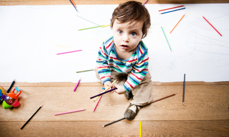 Overhead view of male toddler sitting on floor with coloured pencils and long paper LANG_EVOIMAGES