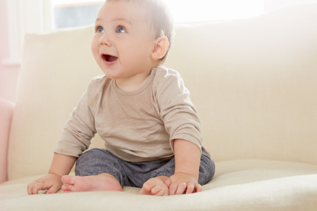 6 12 months: Baby boy looking up from sofa