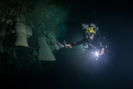 morelos: Scuba diver exploring unique natural formations known as bells in submerged caves beneath the jungle