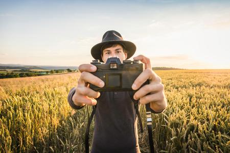 Mid adult man, standing in field, taking selfie with SLR camera, Neulingen, Baden-Württemberg, Germany