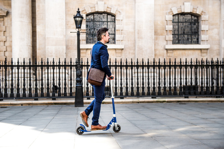 Businessman on scooter, London, UK LANG_EVOIMAGES