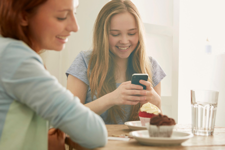 Girl in cafe looking at smartphone smiling