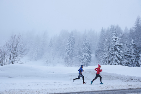 Distant view of female and male runners running in deep snow, Gstaad, Switzerland