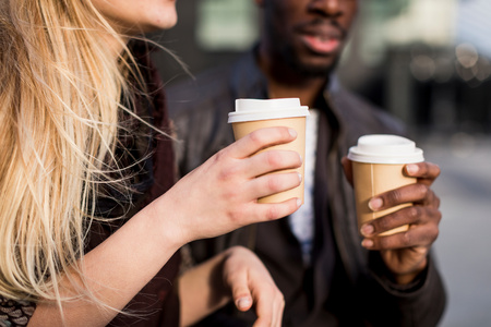milánó: Cropped shot of young couple holding takeaway coffee in city