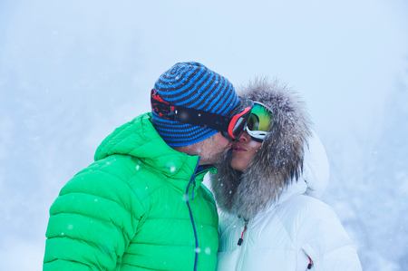Mature couple kissing in falling snow, Gstaad, Switzerland