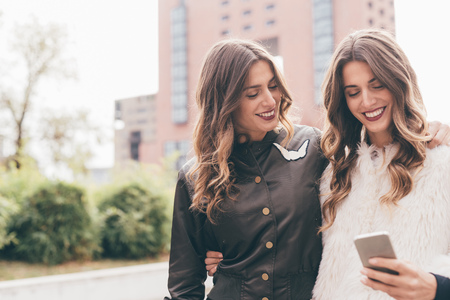 identical: Twin sisters, walking outdoors, looking at smartphone, smiling