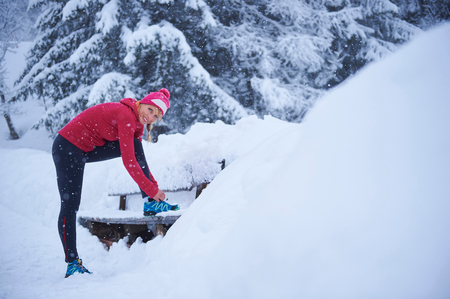 Portrait of female runner tying trainer laces on park bench in deep snow, Gstaad, Switzerland