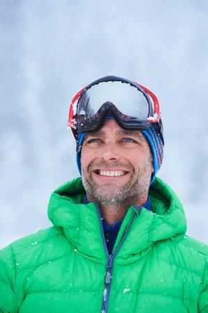 Portrait of happy mature man in falling snow, Gstaad, Switzerland