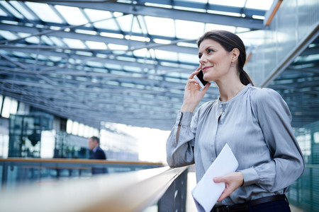 Businesswoman making smartphone call on office balcony LANG_EVOIMAGES