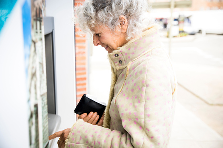 personal identification number: Mature woman pressing PIN at local french cash machine LANG_EVOIMAGES