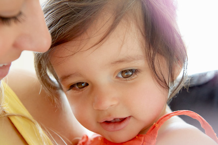 6 12 months: Close up of brown eyed baby girl and mother LANG_EVOIMAGES