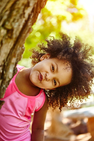 Portrait of young girl, peering out from behind tree, smiling