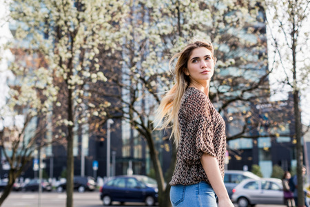milánó: Young woman looking over her shoulder in city LANG_EVOIMAGES