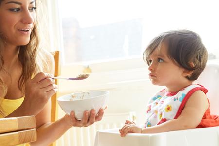 stubbornness: Woman feeding breakfast cereal  to stubborn baby girl