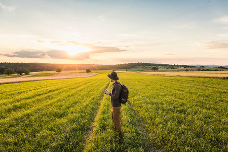 Mid adult man, standing in field, holding SLR camera, looking at view, Neulingen, Baden-Württemberg, Germany