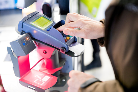 personal identification number: Mature woman using credit card machine to pay for shopping, close-up