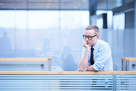 Stressed businessman with chin on hand in office atrium LANG_EVOIMAGES