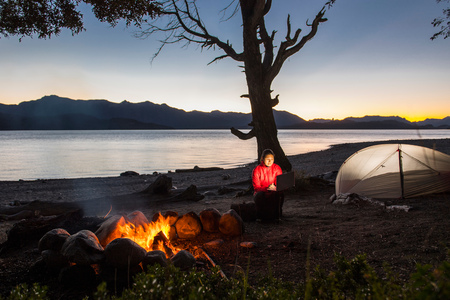 Woman looking at her laptop by a campfire at Nahuel Huapi Lake in Patagonia LANG_EVOIMAGES
