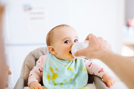 6 12 months: Father feeding baby daughter