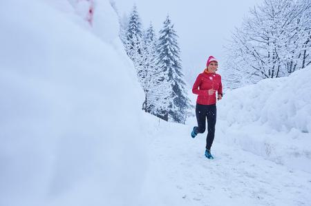 Female runner running on track in deep snow, Gstaad, Switzerland