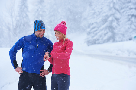 Female and male runners checking smartwatch on deep snow track, Gstaad, Switzerland LANG_EVOIMAGES