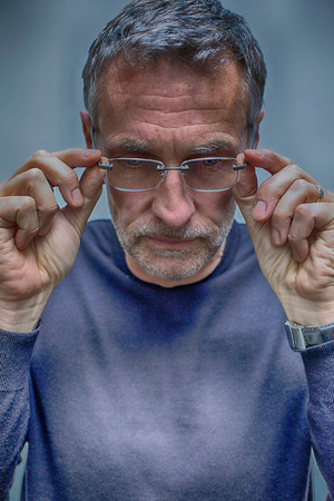 graying: Portrait of greying mature man removing glasses
