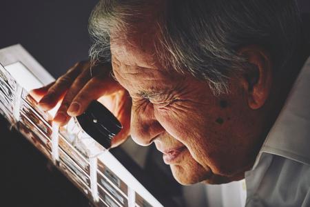 Senior man looking at sheet of film slides with magnifier LANG_EVOIMAGES